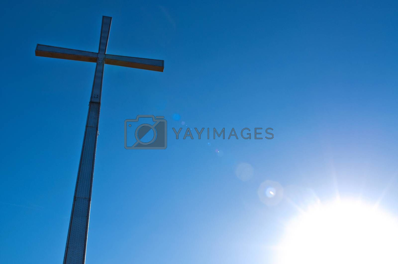 cross with sky and sun in the background