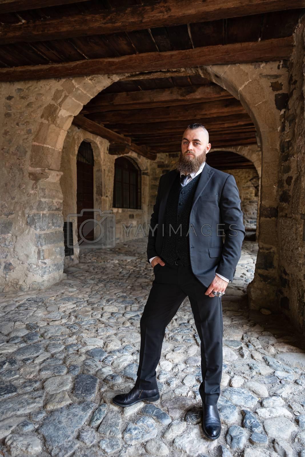 Man in dark elegant suit posing under the arcades of a medieval Italian village, full-length male portrait