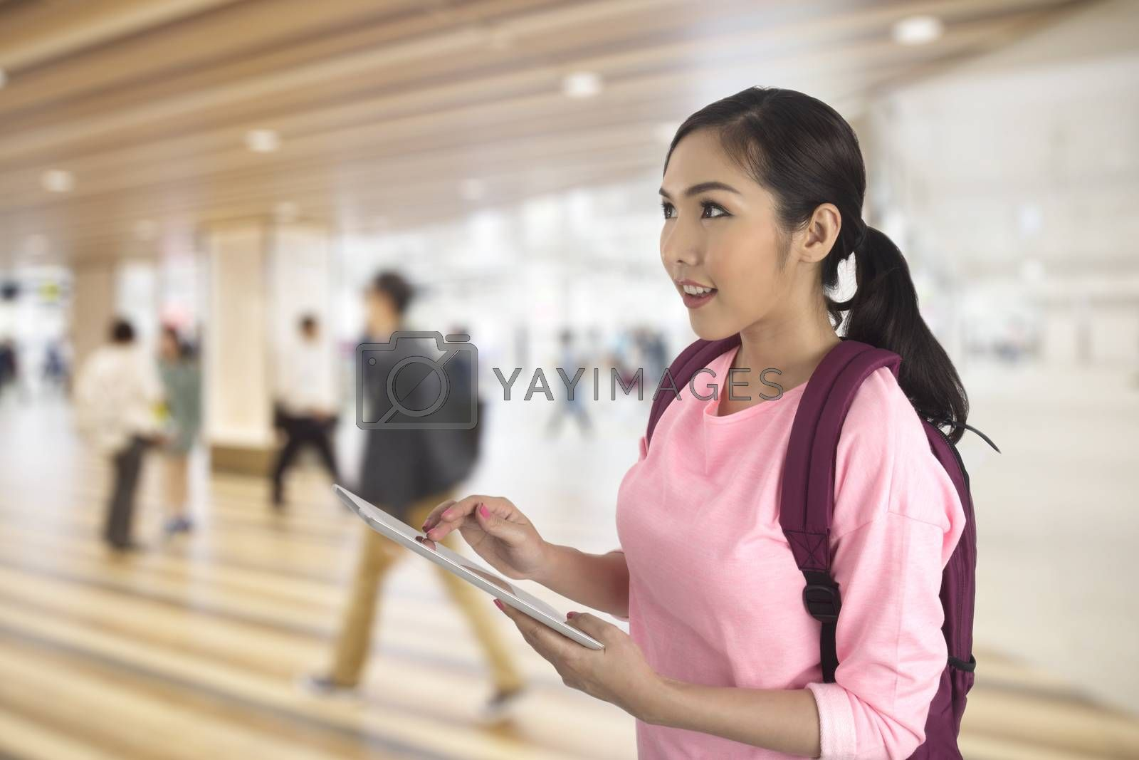 Tourist girl standing on walkway in building using computer tablet finding traveling information.