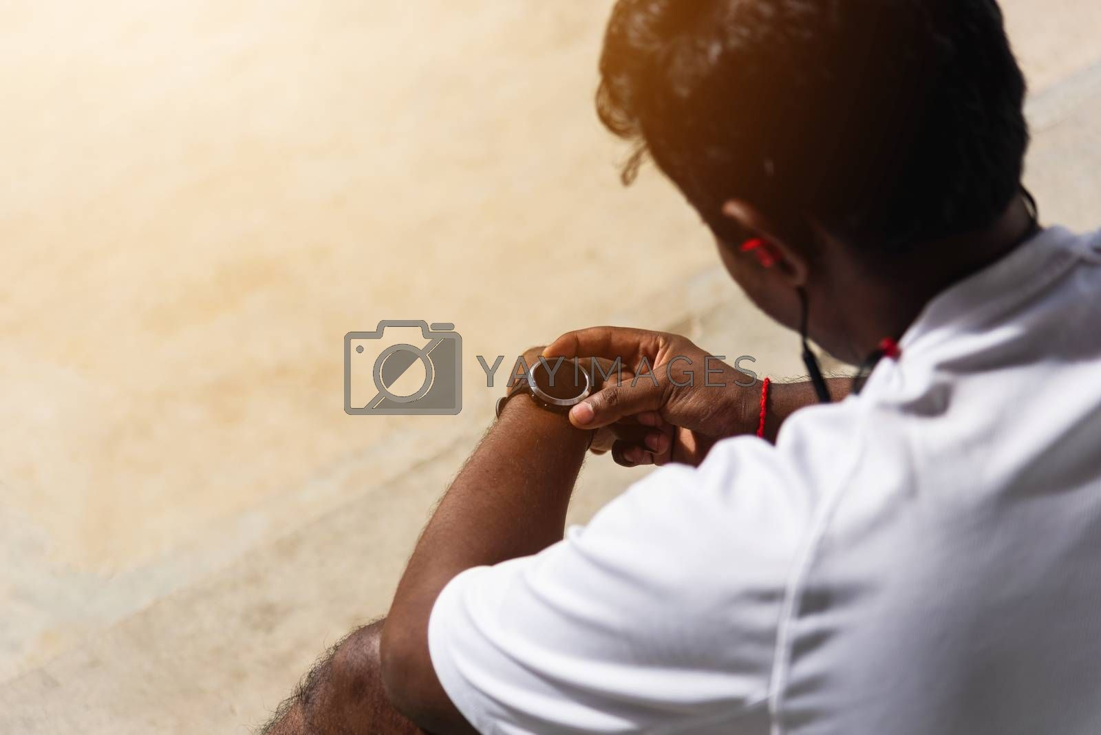 Close up Asian young athlete sport runner black man wear modern time smart watch he sitting resting before training running at the outdoor street health park, healthy exercise before workout concept