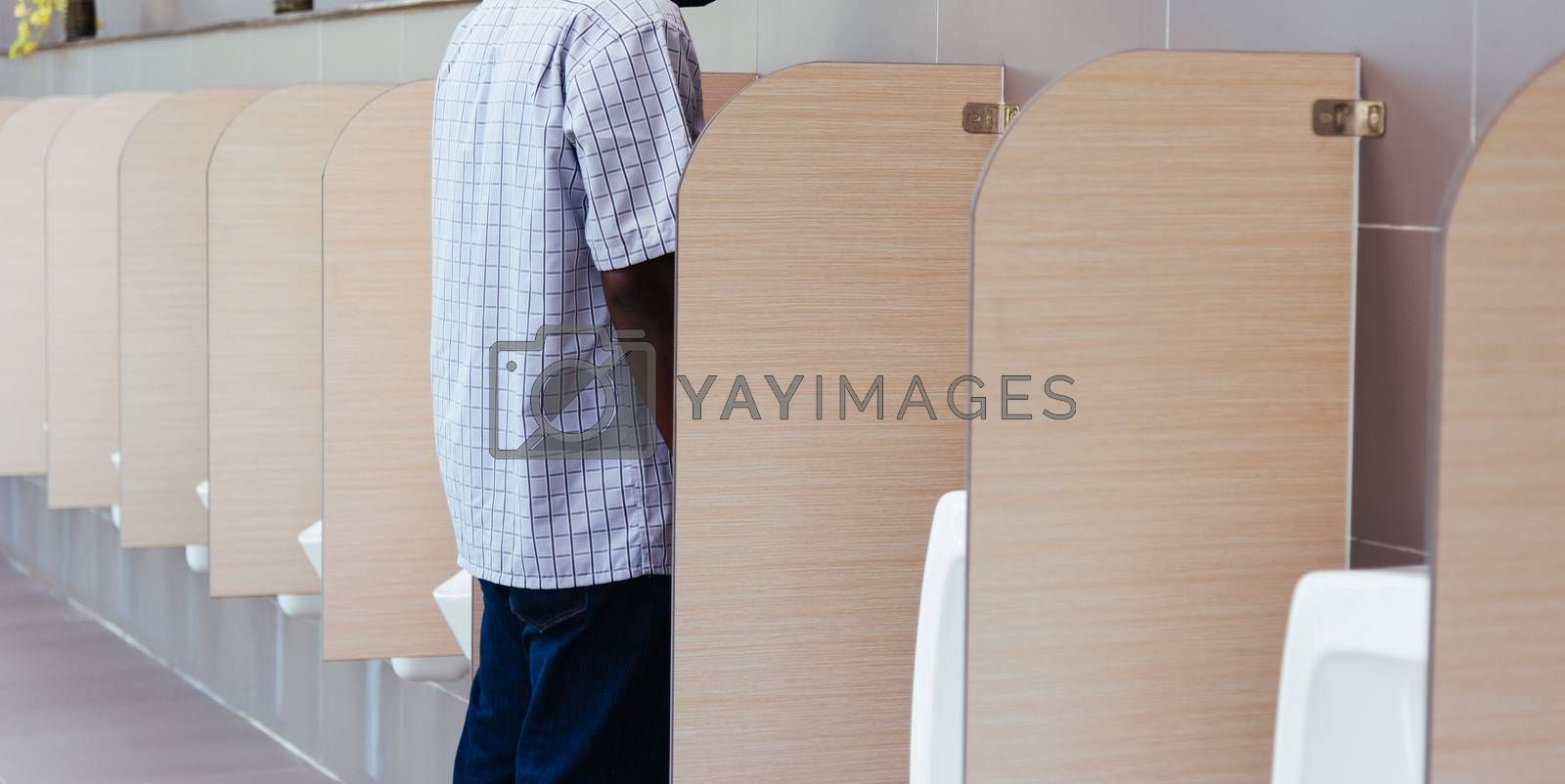 The man peeing in male toilet urinals bowl in restroom, wc