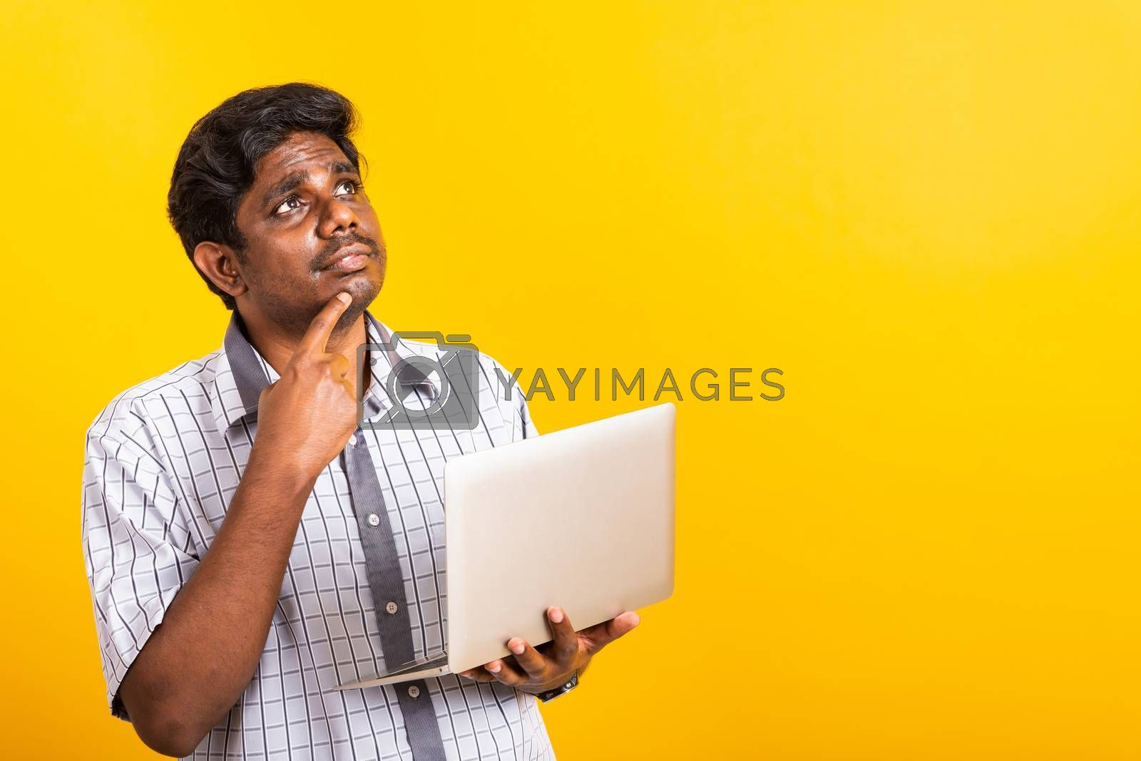 Closeup Asian happy portrait young black man holds a laptop computer hand finger handle on the chin and thinking question looking away, studio isolated on yellow background