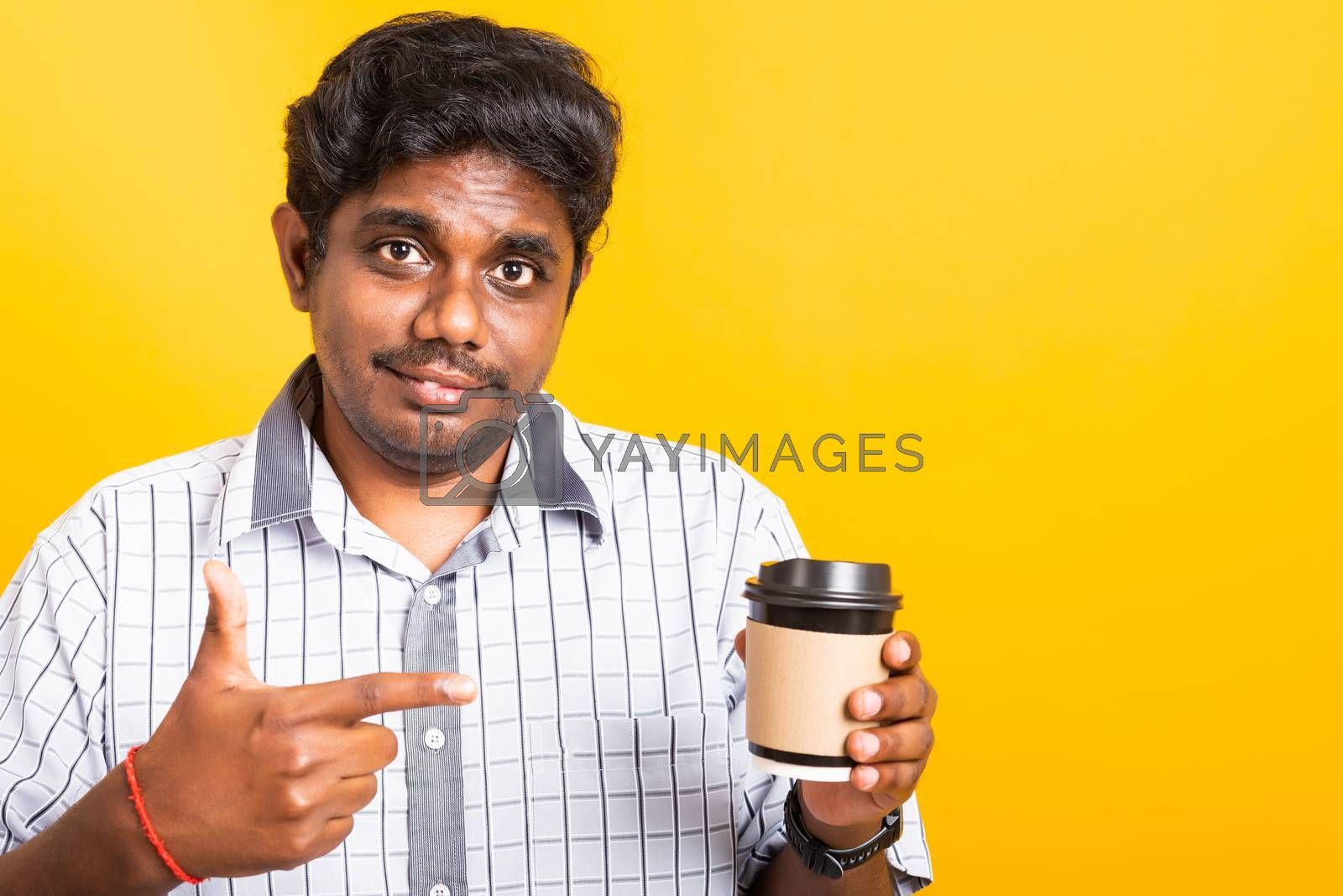 Closeup Asian happy portrait young black man smile holding coffee cup take away and pointing hand finger to coffee cup, studio isolated on yellow background