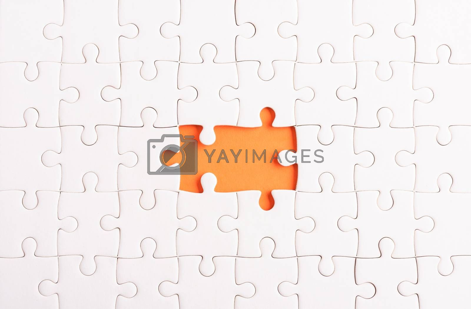 Top view flat lay of paper plain white jigsaw puzzle game texture incomplete or missing piece, studio shot on an orange background, quiz calculation concept