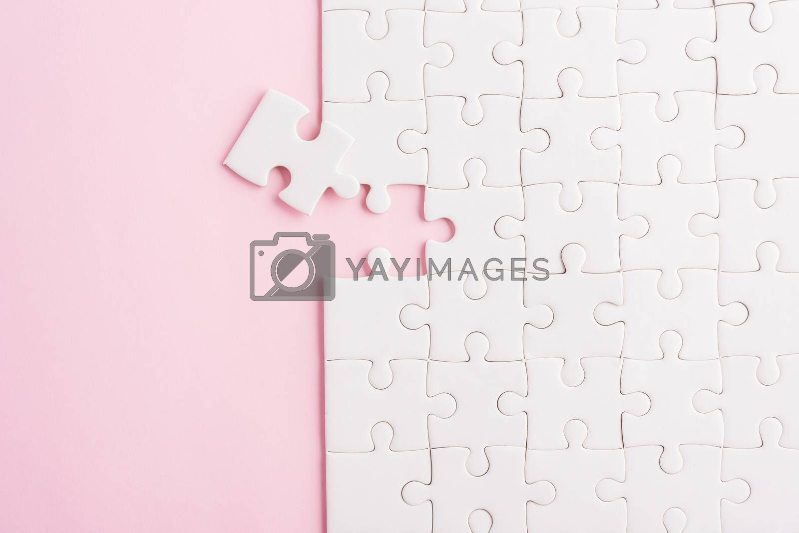 Top view flat lay of paper plain white jigsaw puzzle game texture last pieces for solve and place, studio shot on a pink background, quiz calculation concept