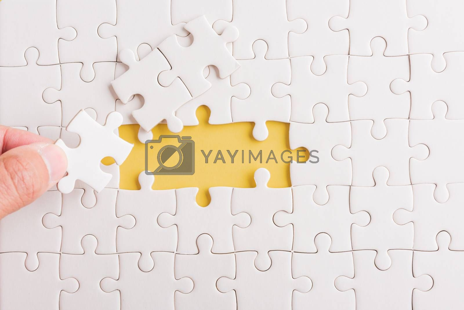 Top view flat lay of hand-holding last piece white paper jigsaw puzzle game last pieces put to place for solve problem complete mission, studio shot on a yellow background, quiz calculation concept