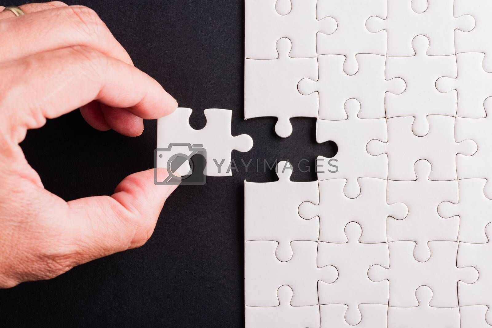 Top view flat lay of hand-holding last piece white paper jigsaw puzzle game last pieces put to place for solve problem complete mission, studio shot on a black background, quiz calculation concept