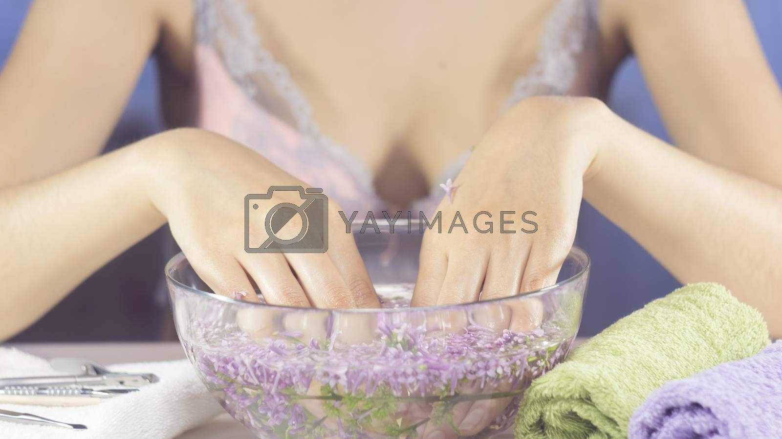Hands of a woman in a bath with flowers. Manicure, nail SPA. Sensuality, skincare, feminine, salon, wash, wealth, therapy, cosmetics, treatment, relax, dayspa, aromatherapy