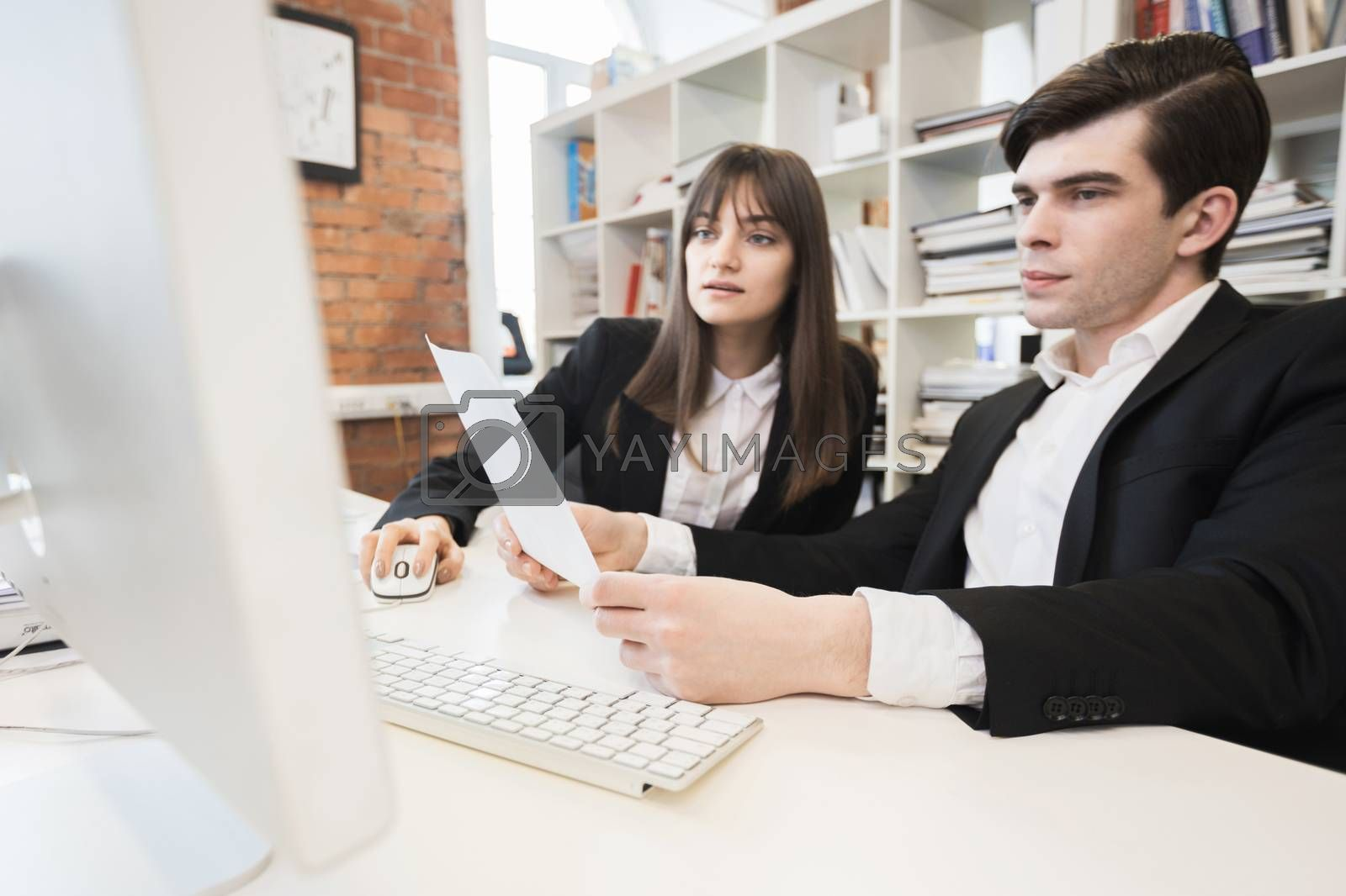Two business people working together with documents sitting in front of computer monitor in office