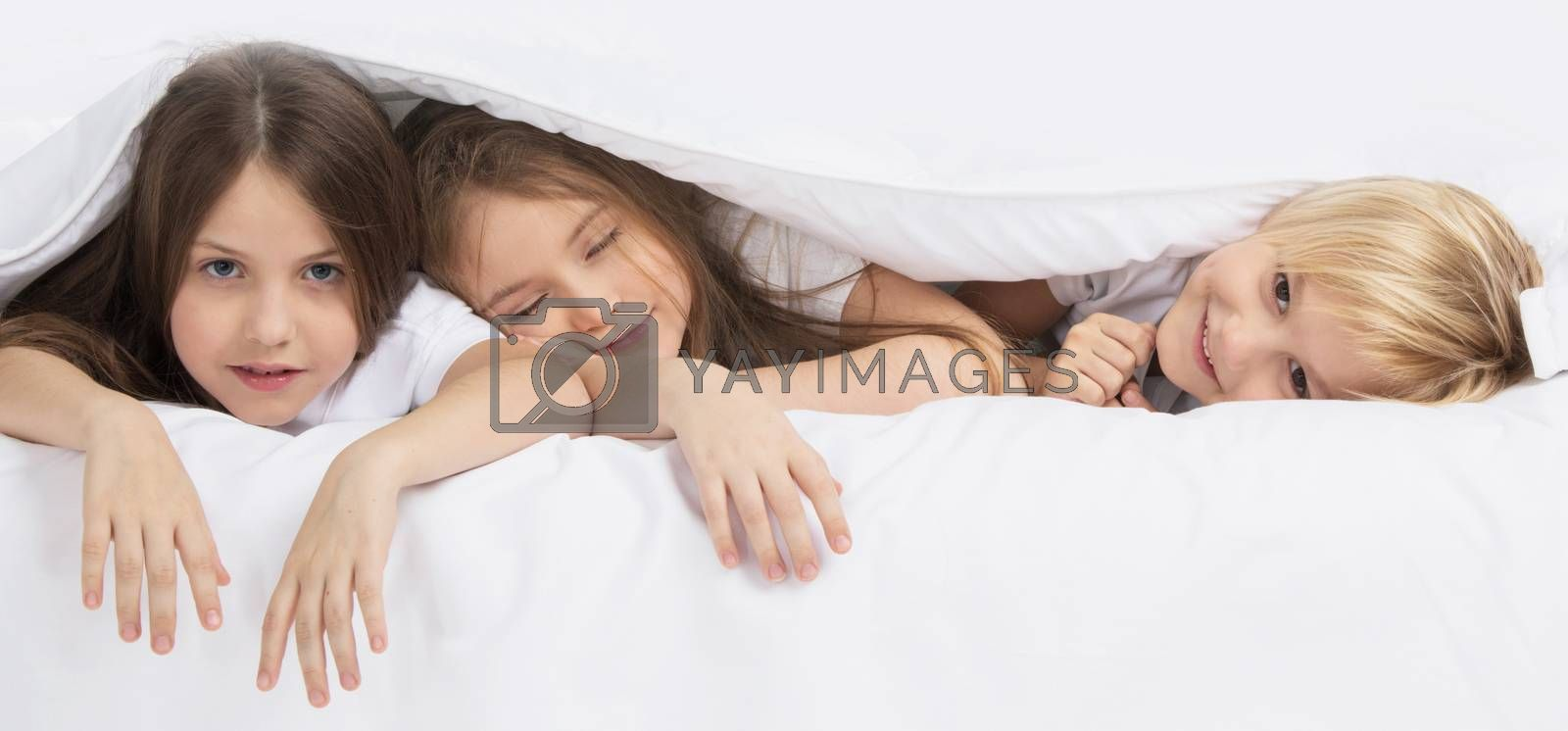 Health, beauty and childhood concept - three smiling children waking up in bed under one blanket at home