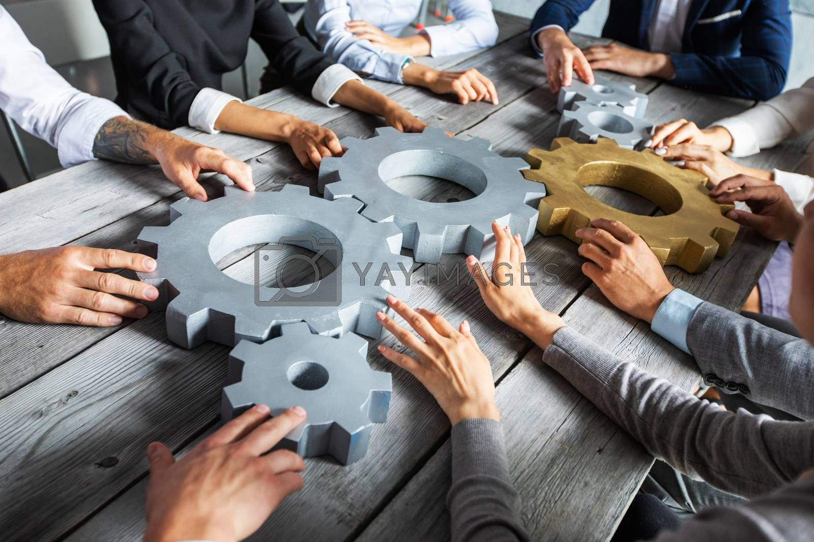 Group of business people joining together silver and golden colored gears on table at workplace