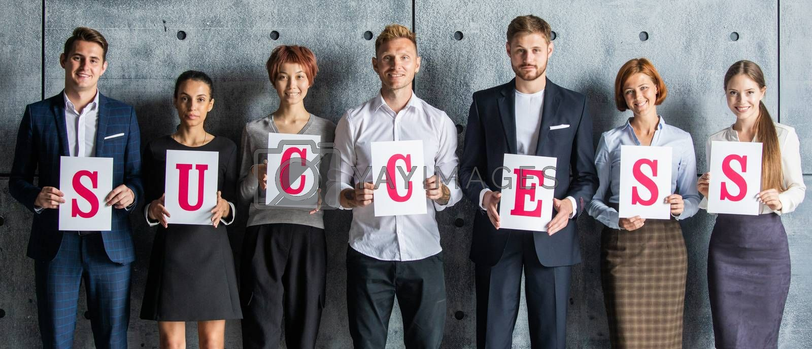 Business people holding SUCCESS letters printed on paper