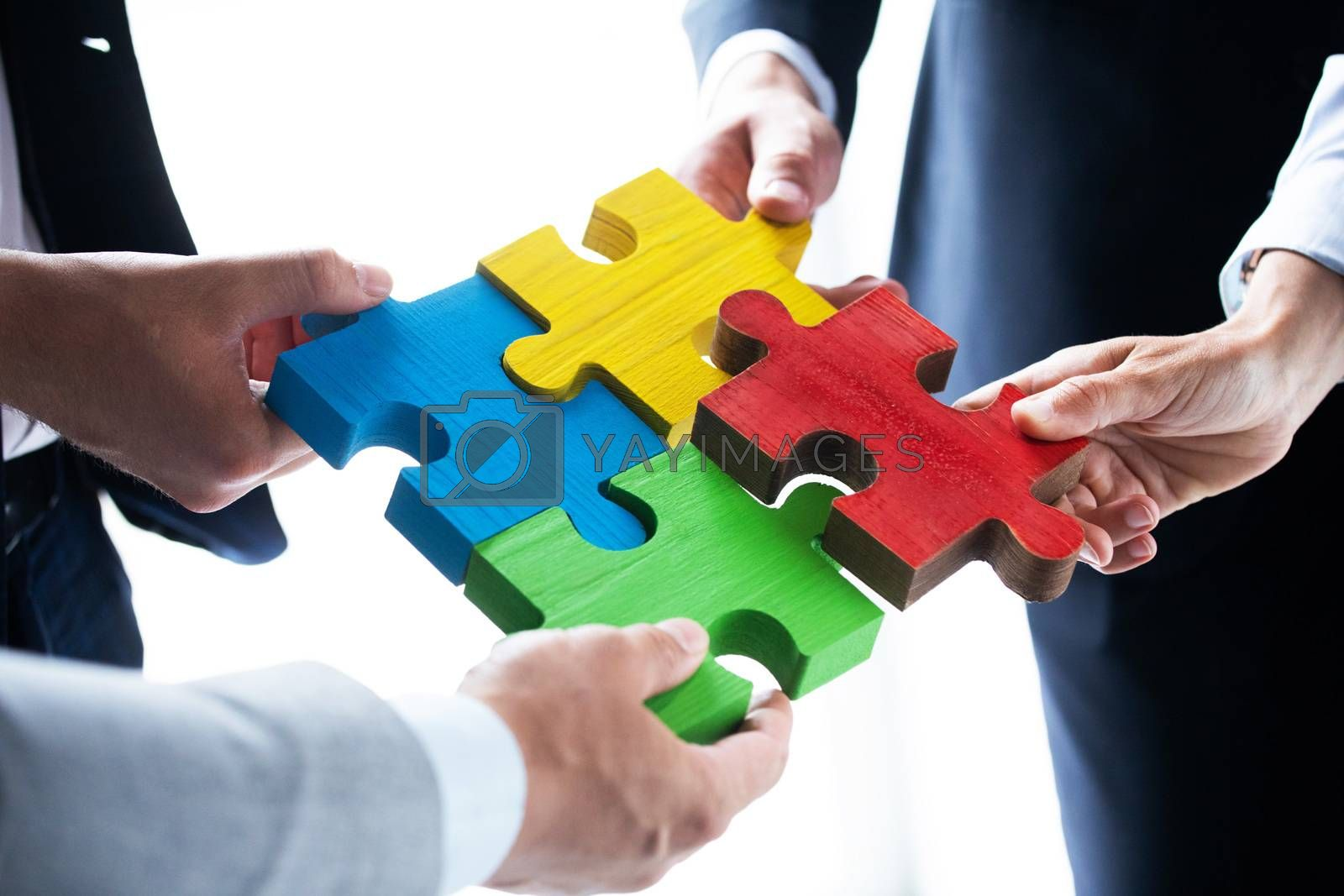 Business people team assembling four color jigsaw puzzle pieces unity cooperation ideas concept