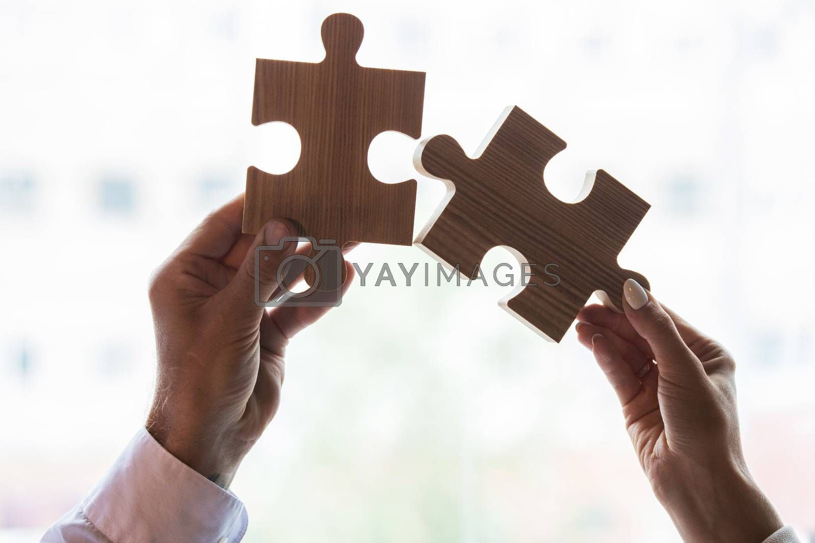 Male and female hands with puzzle pieces on white, business cooperation problem solution relationship concept