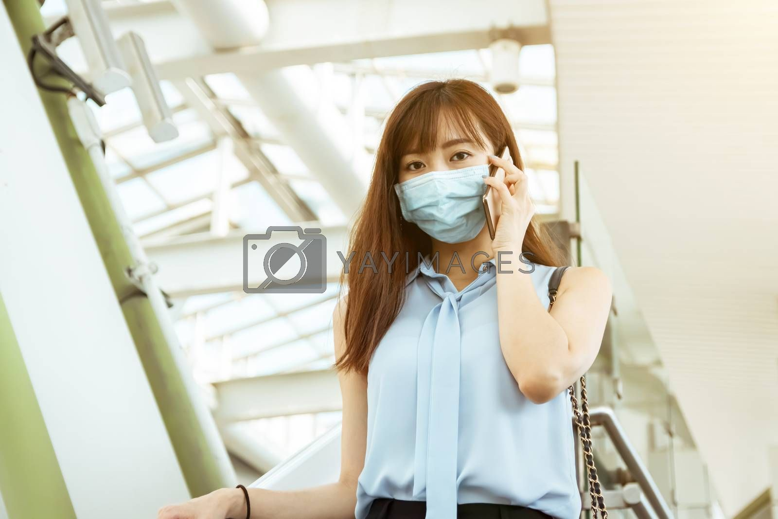 business woman wearing face mask at train station talking on the mobile phone