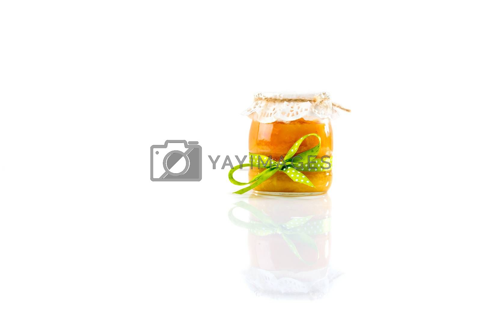 Glass jar with apricot jam isolated on white background.