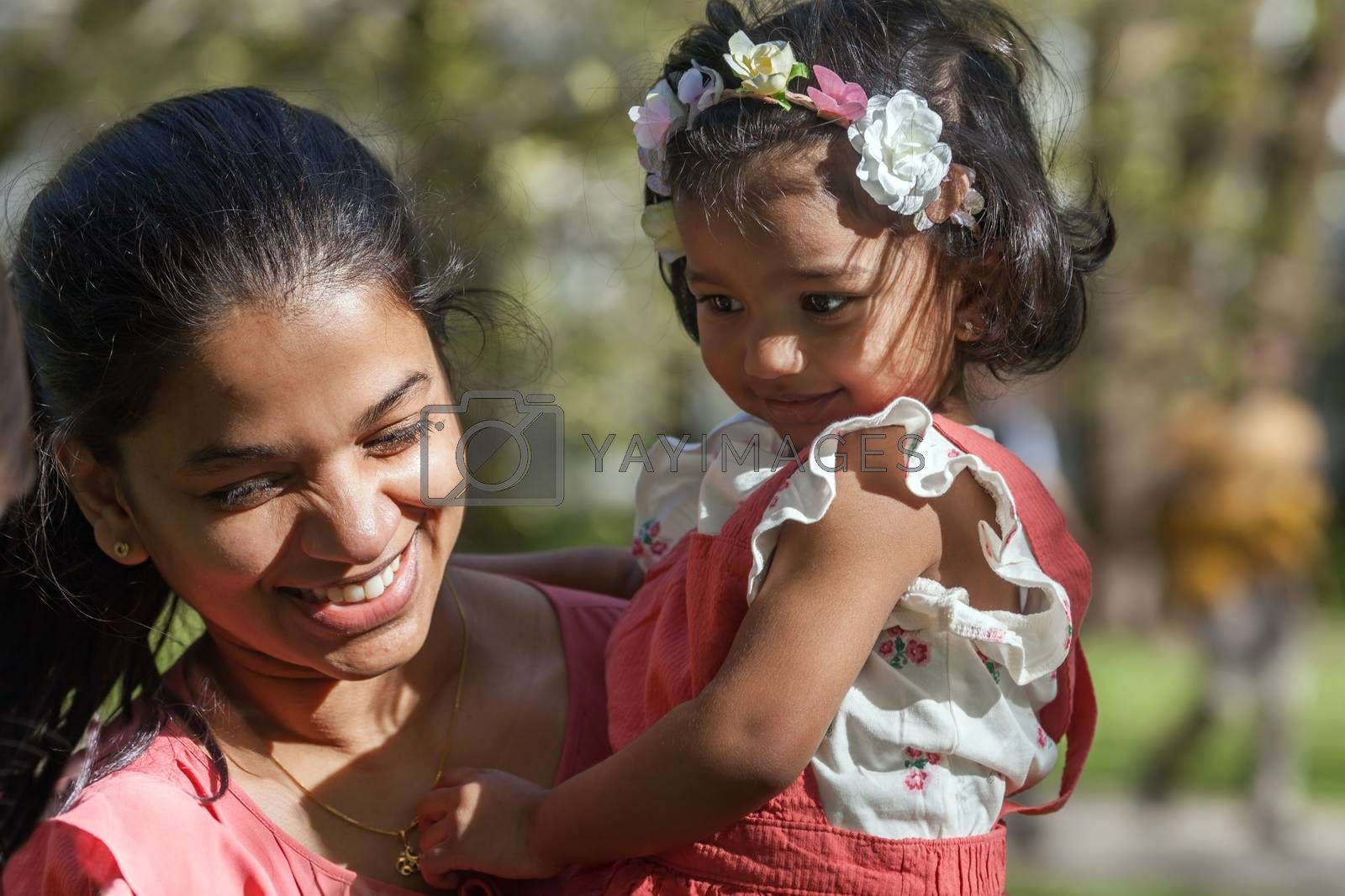 A happy south asian female with two years old girl in spring park