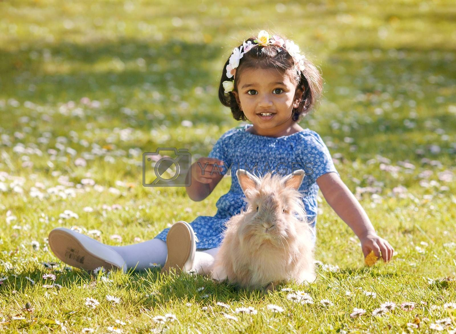 A small Asian girl is sitting with home rabbit on green grass in spring park