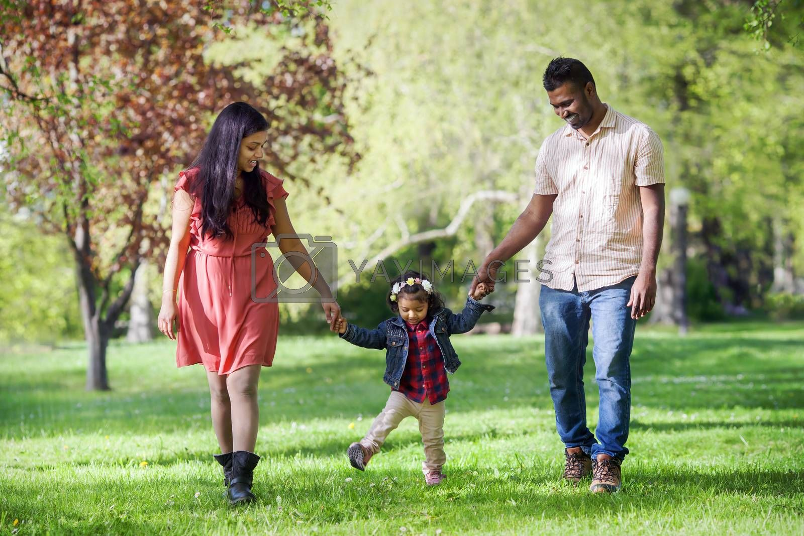 Father, mother and two years old girl are walking in sunny spring park