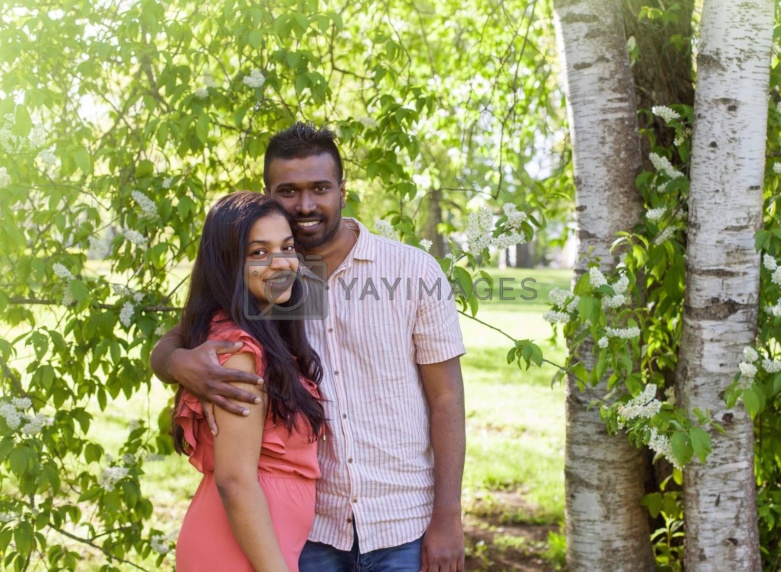A south asian happy young couple is walking in city park