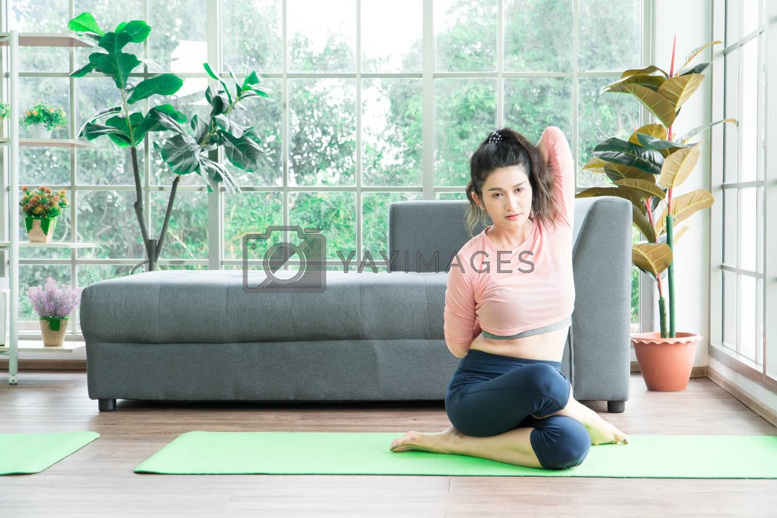 Attractive and healthy woman Asian are exercising Stretching with yoga postures at home helps to balance life. copy space is on the right side of the image For adding text
