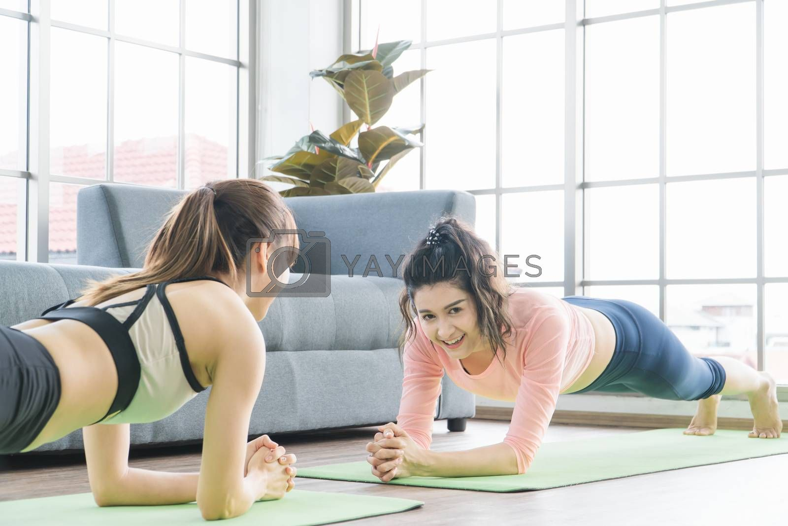 Attractive and healthy women Two Asians Exercising Stretching the muscles with yoga postures together at home. Help balance life