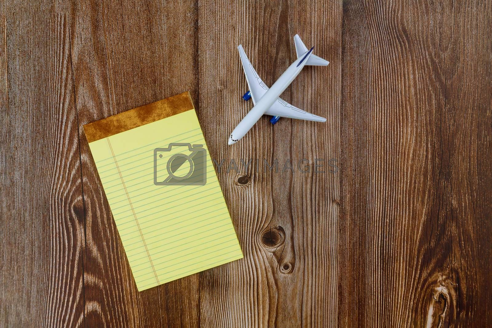 Office traveler with travel planning model plane airplane with blank paper notes,