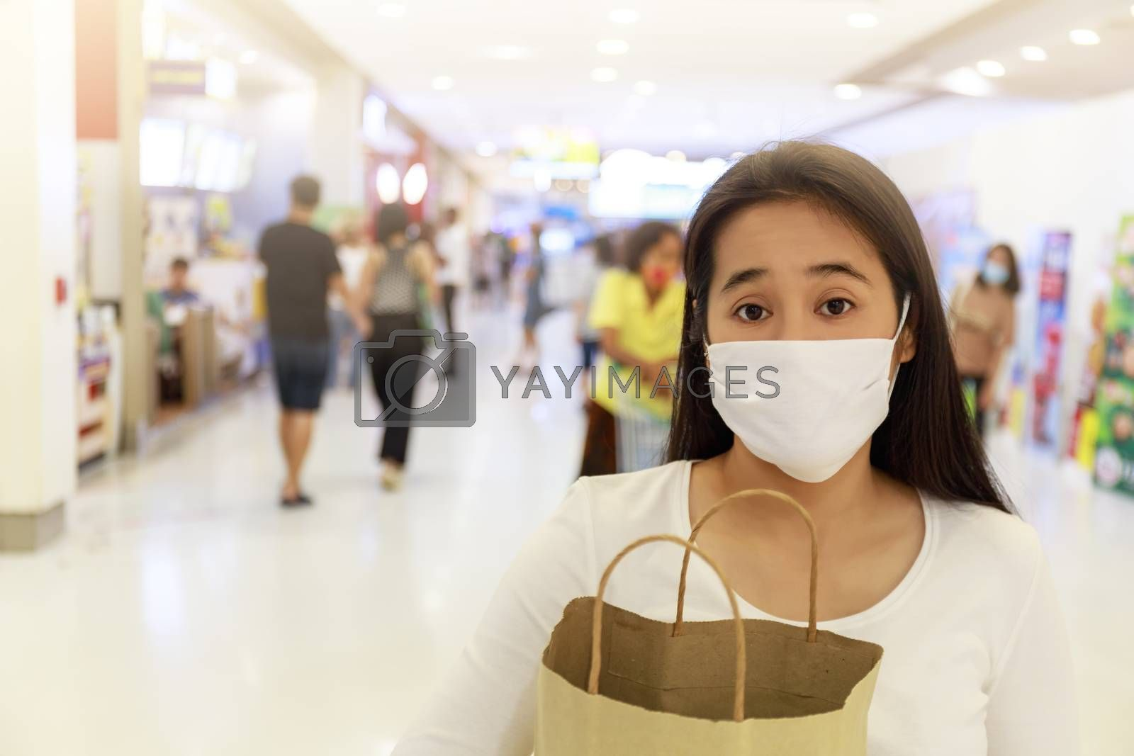 Asian woman long hair wear face mask Holding empty paper shopping bag in supermarket. Girl looking grocery to buy something During coronavirus crisis or covid19 outbreak. new normal concept with copy space.