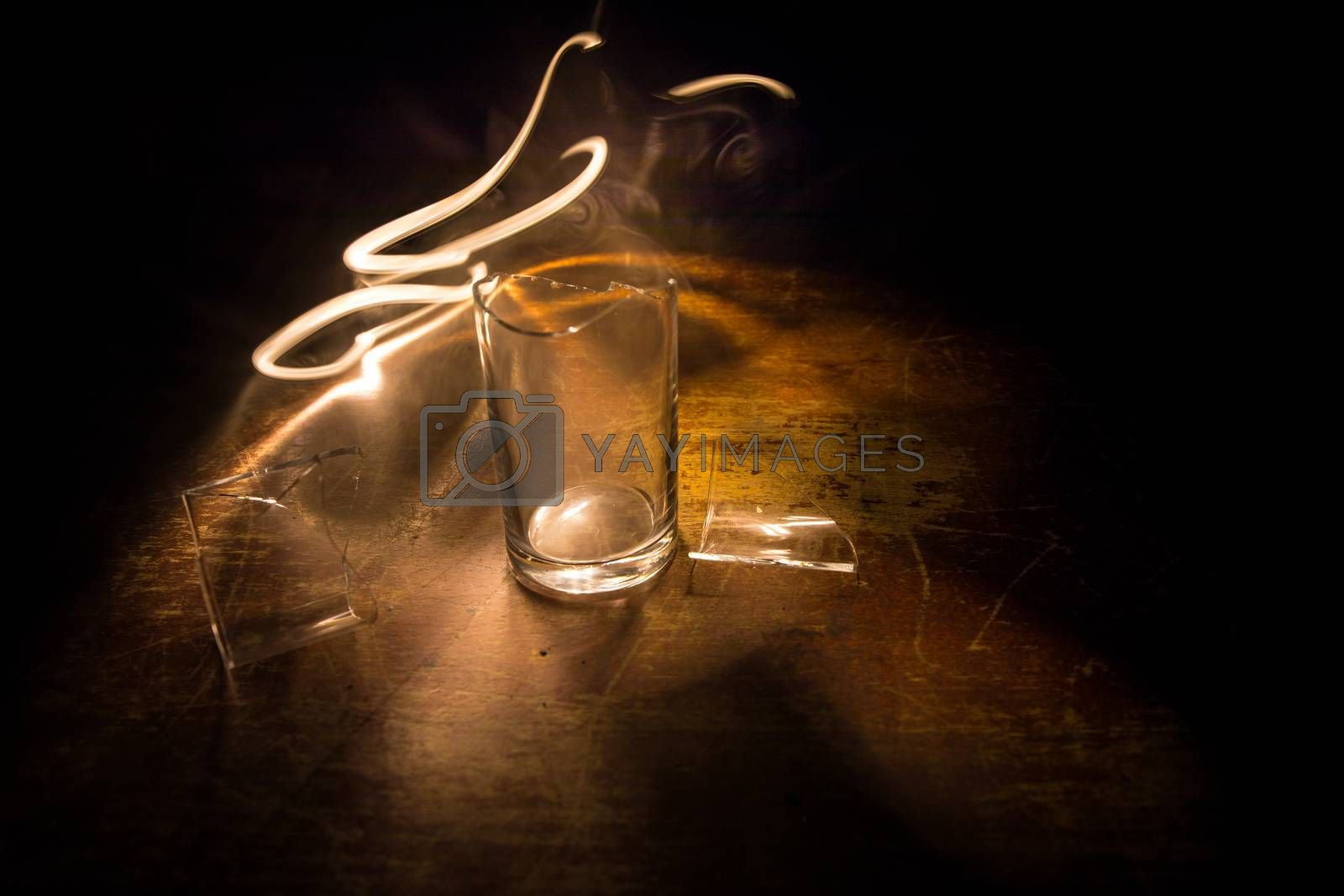 Drink, broken glass concept. Broken glasses on wooden table at dark toned background with fog. Selective focus