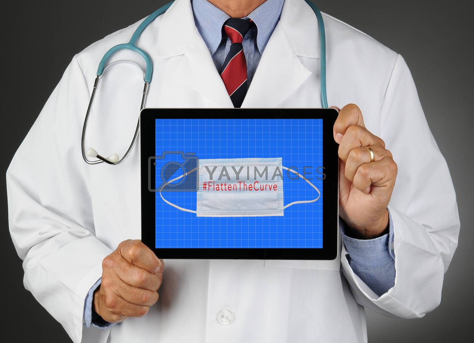 Closeup of a doctor holding a tablet computer with a Surgical mask and Flatten the Curve