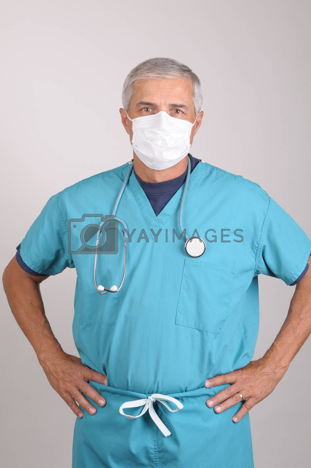 Middle Aged  Doctor in Scrubs and Surgical Mask with Hands on Hips, vertical on gray background