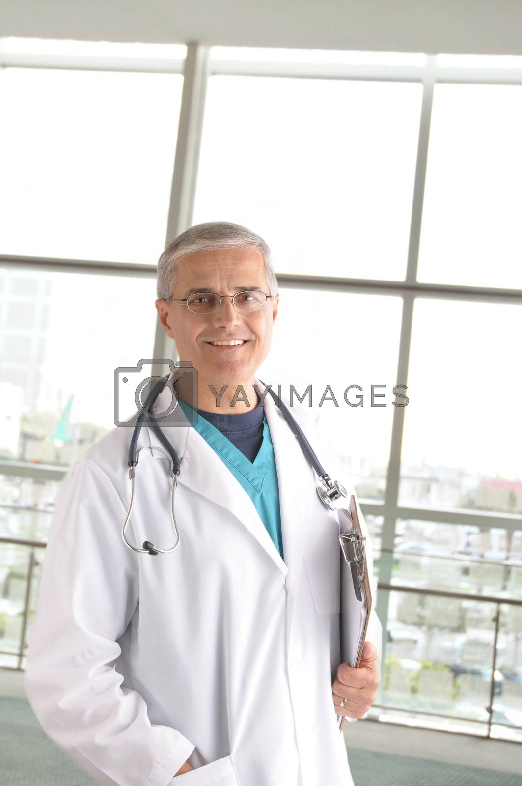Middle aged doctor with stethoscope and clip board standing in front of large window in modern medical facility