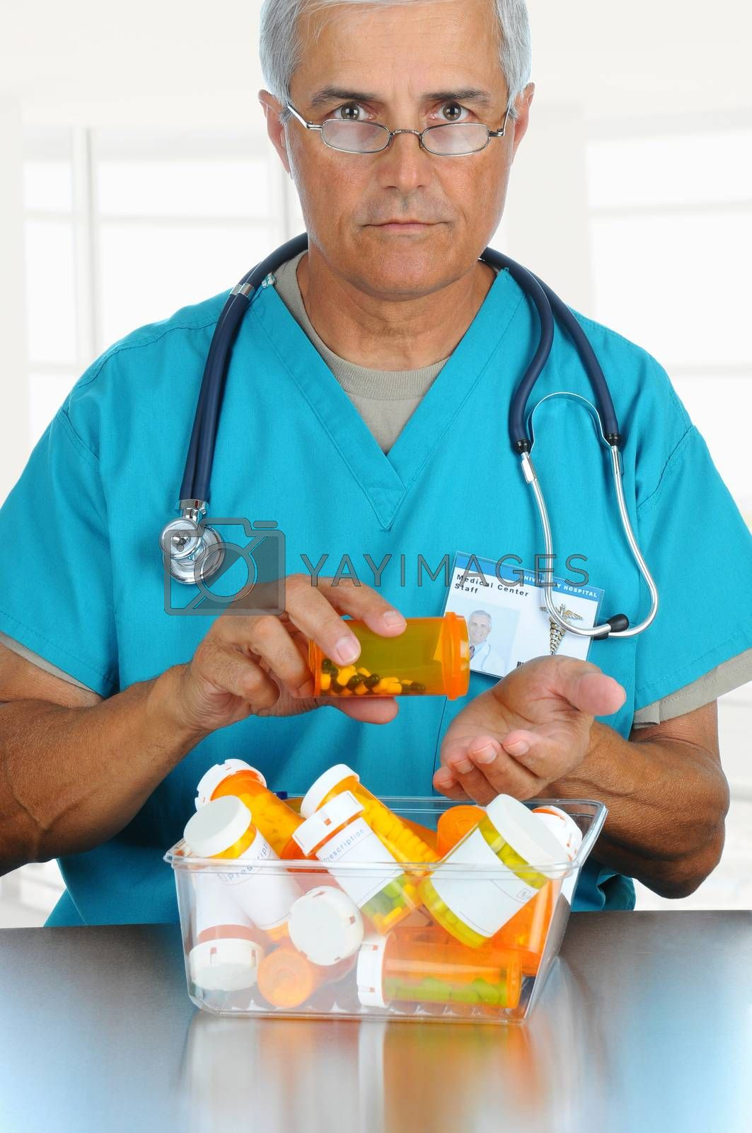 Smiling middle aged doctor pouring prescription medicine from a bottle into his hand. Vertical format in modern office setting.