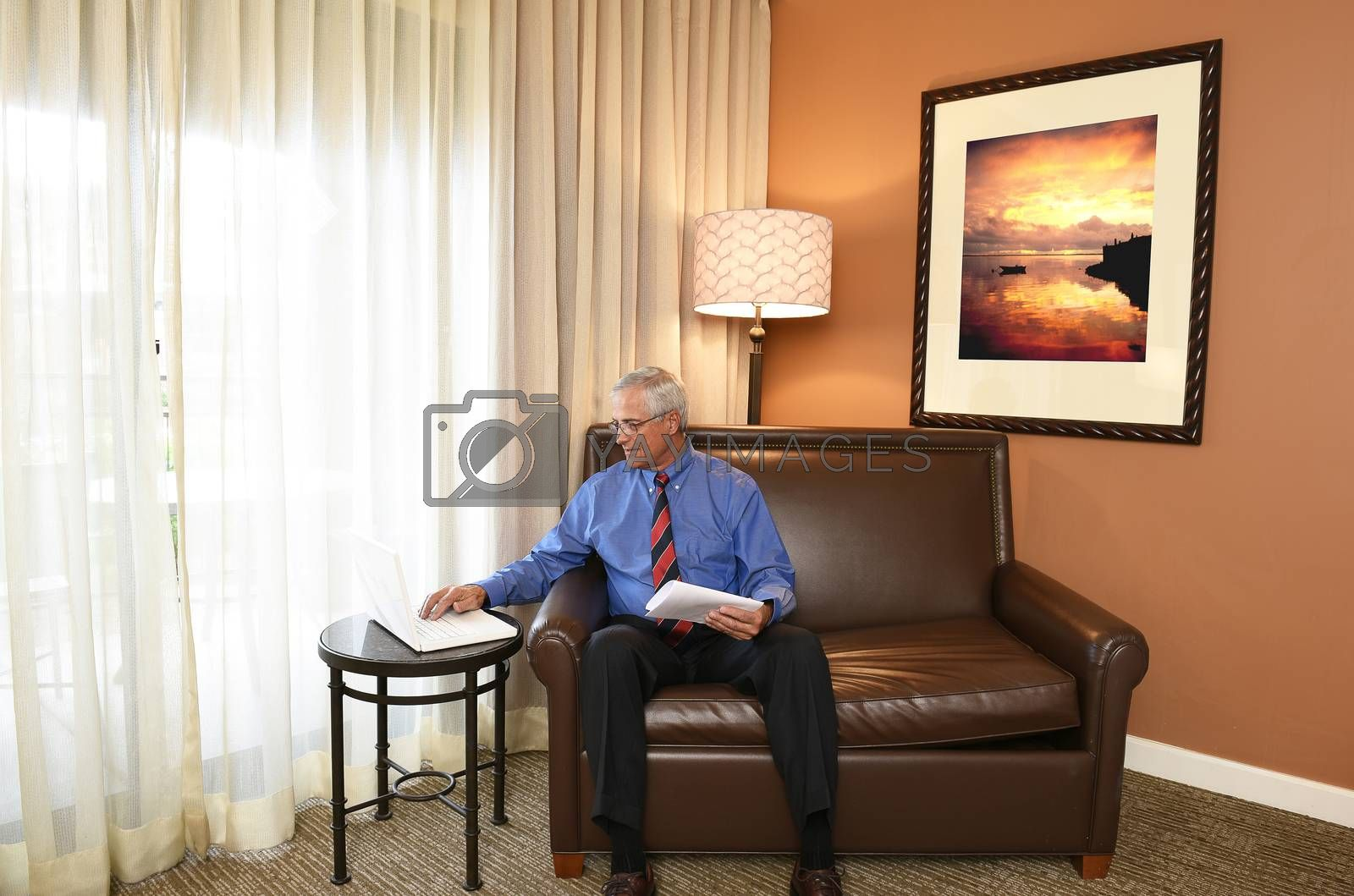 A senior businessman seated on the couch of his hotel room working on his laptop computer.