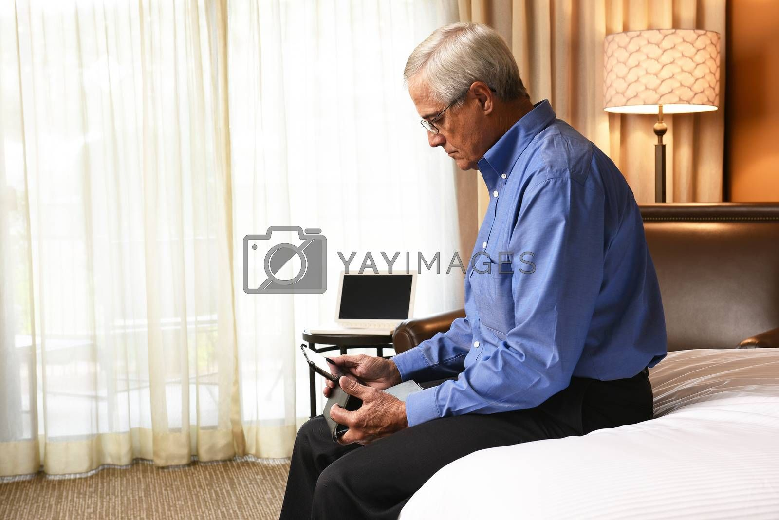 A senior businessman seated on the end of the bed his hotel room while using a tablet computer.