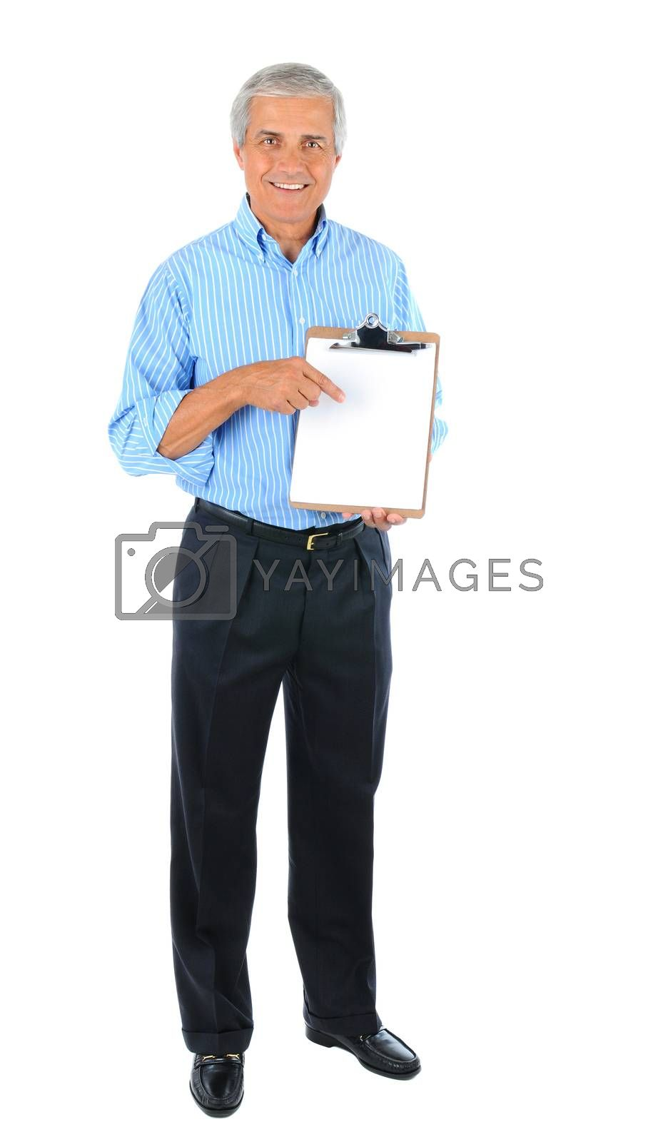 Smiling middle aged businessman standing pointing at a clipboard with a blank piece of paper. Full length over a white background.