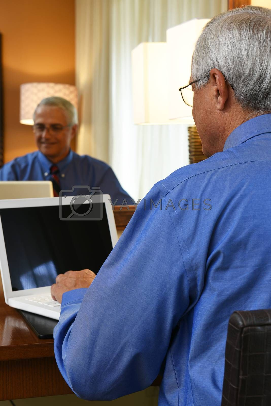 Business Travel Concept: Mature businessman sitting at his hotel room desk working on his laptop computer with his reflection in the mirror.
