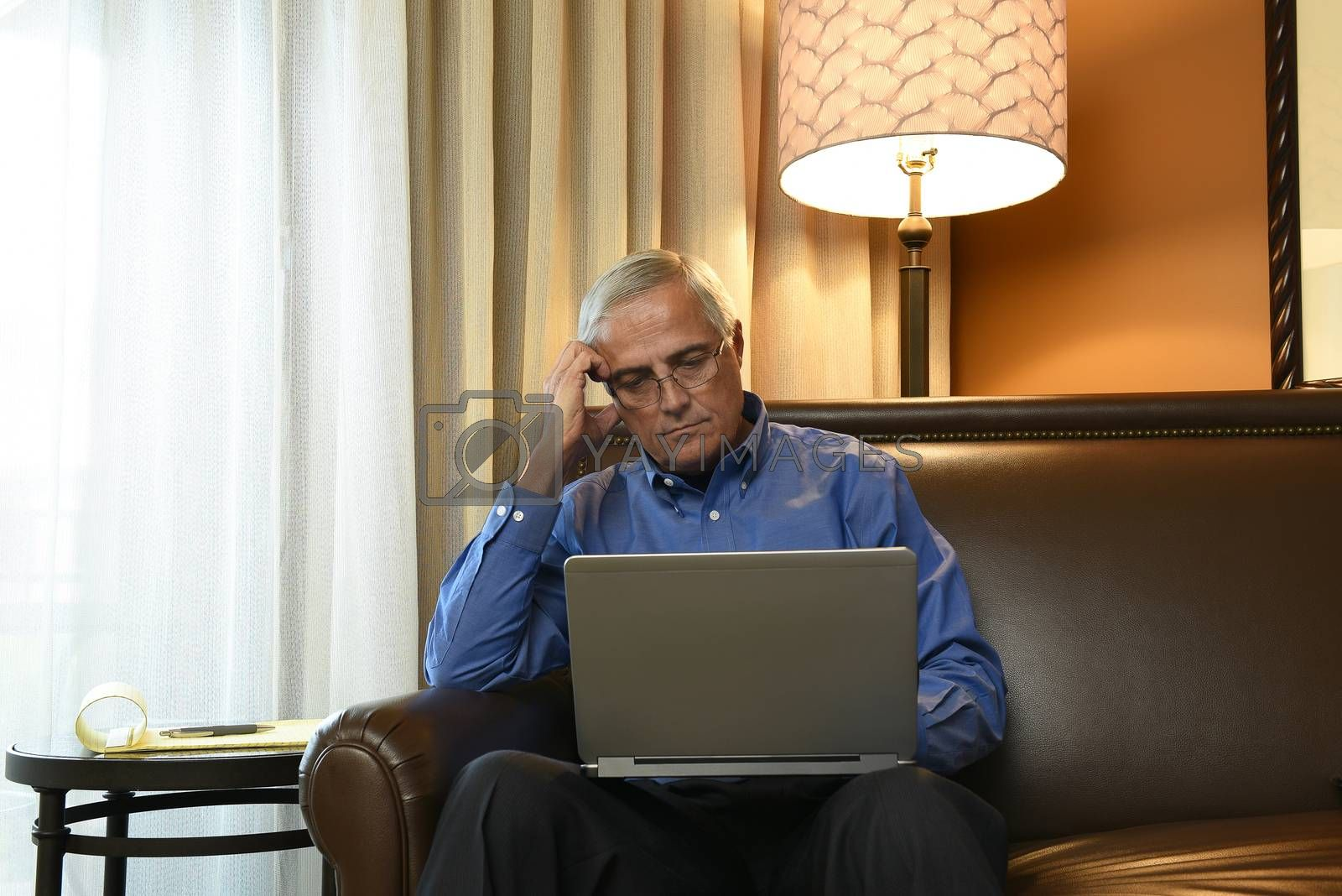 Business Travel Concept: Mature Businessman sitting in his hotel room working on his laptop computer.