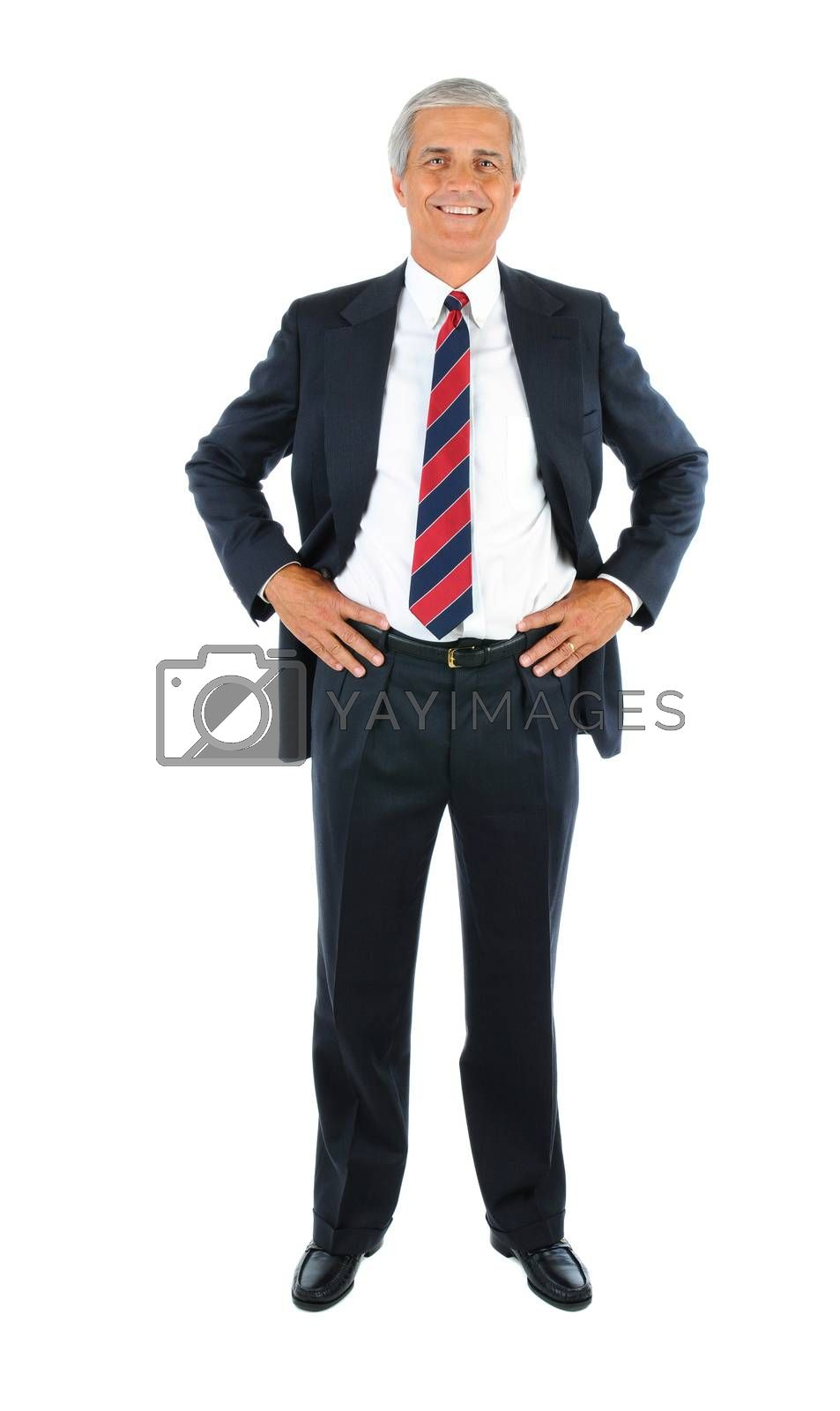 Smiling middle aged businessman in a suit and tie with his hands on hips. Full length over a white background.