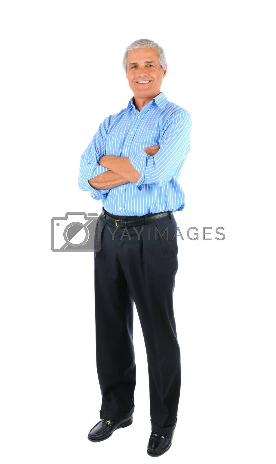 Smiling middle aged businessman standing with his arms folded. Full length over a white background.