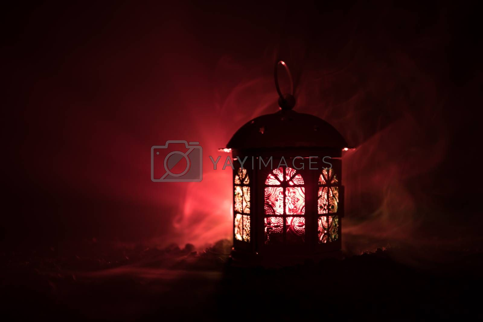 Love Valentine`s Day greeting card decoration photo. Candle lighting lamp lantern glowing on dark colorful foggy background. Selective focus