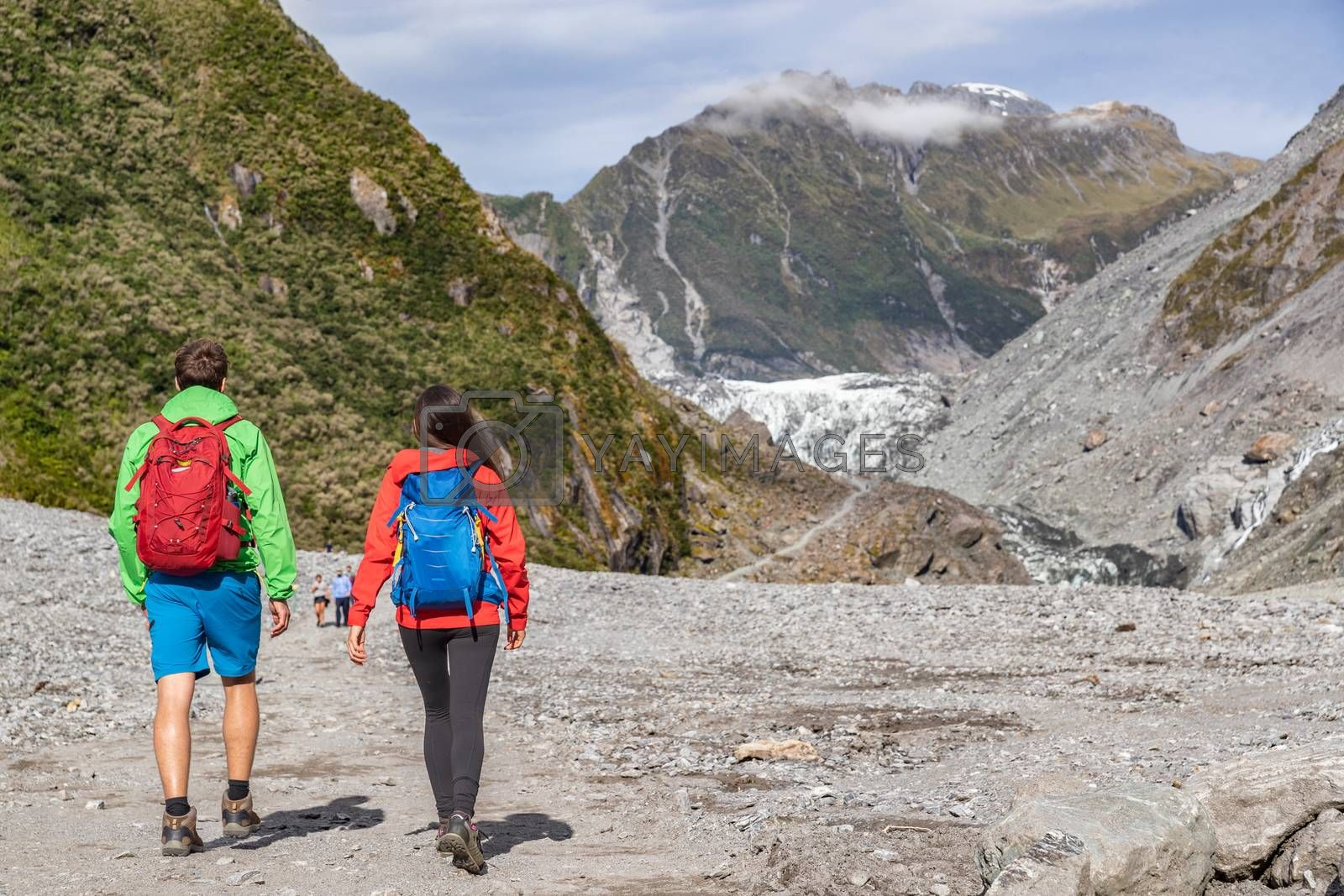 New Zealand tourists backpacking in nature landscape by Franz Josef Glacier, Westland Tai Poutini National Park, South Island, New Zealand. Couple on travel arriving at famous viewpoint.