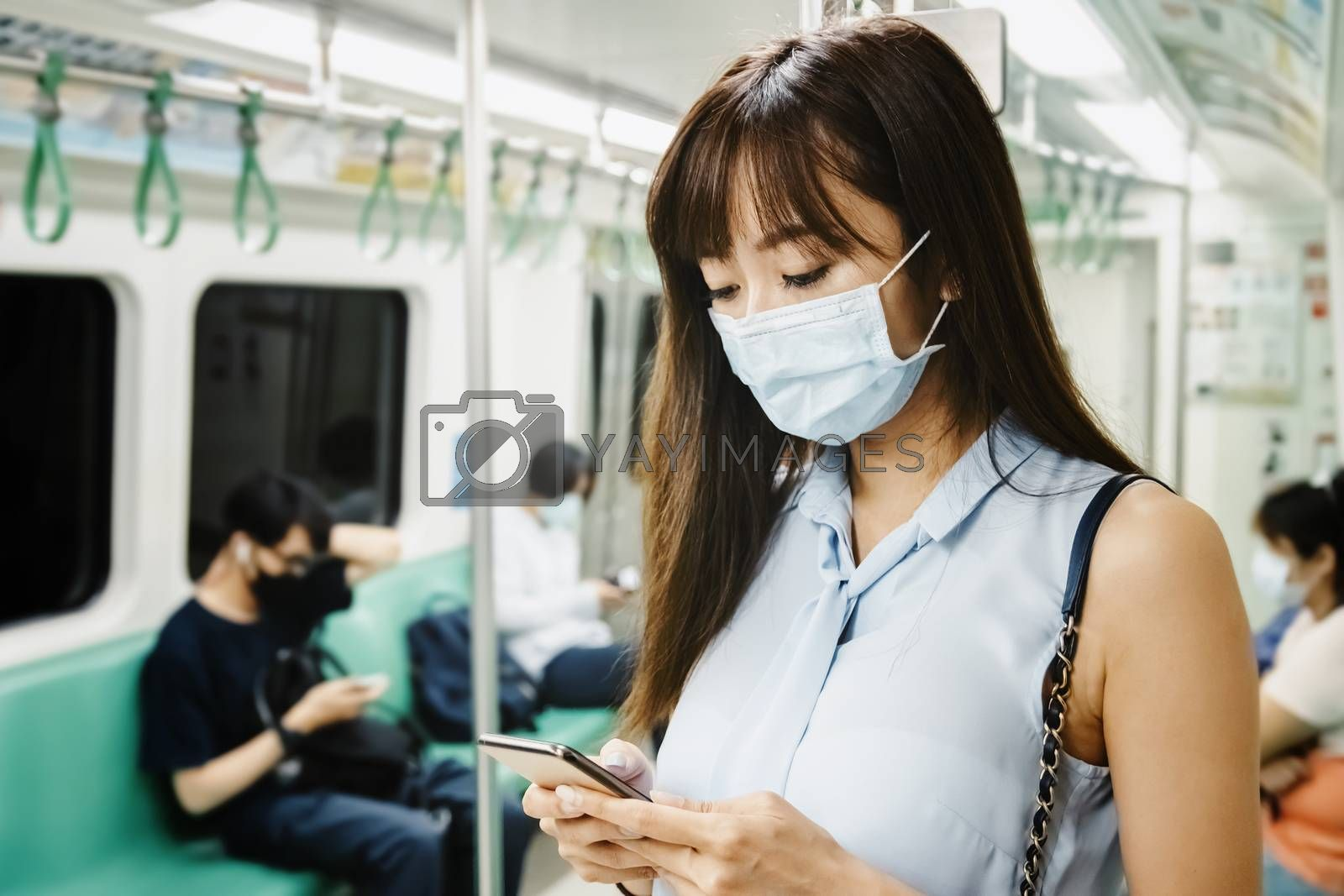 Young Asian woman passenger wearing surgical mask and using mobile phone in subway train
