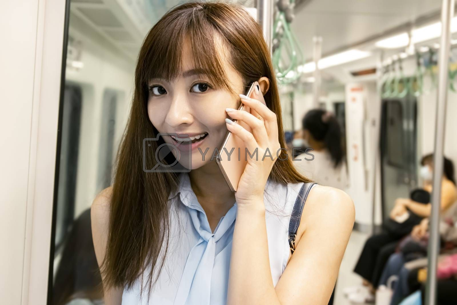 young woman talking on the phone in  subway train