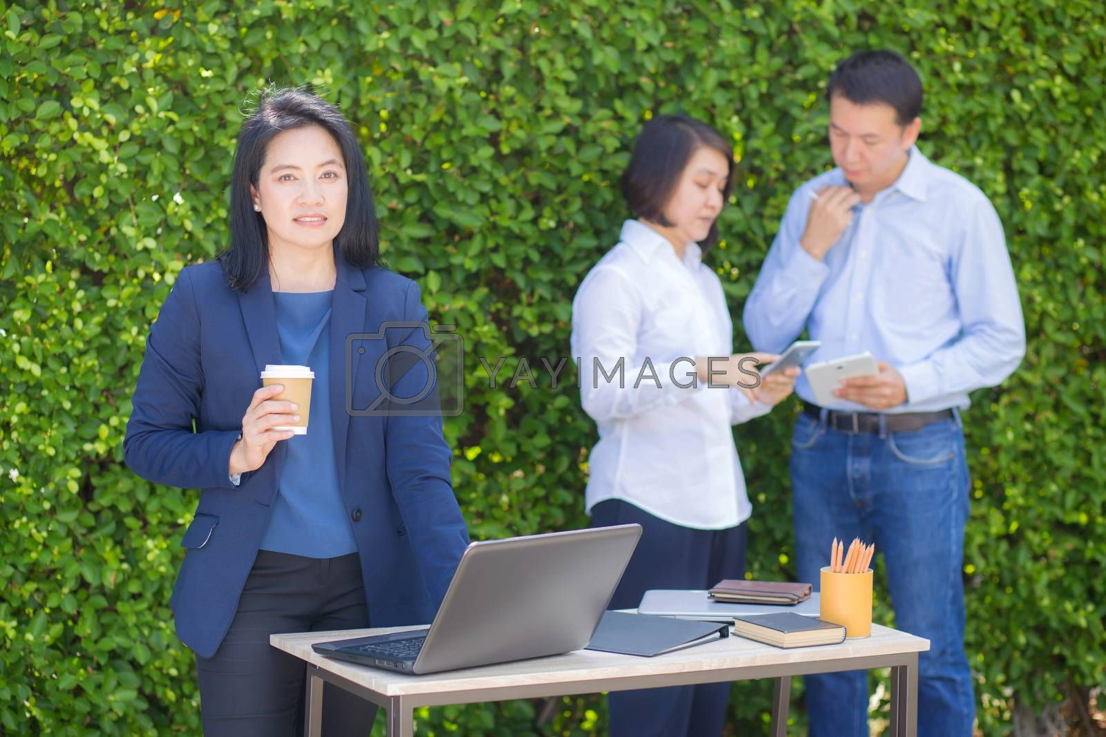 Young attractive businesswoman with the notebook in the garden tree wall background.