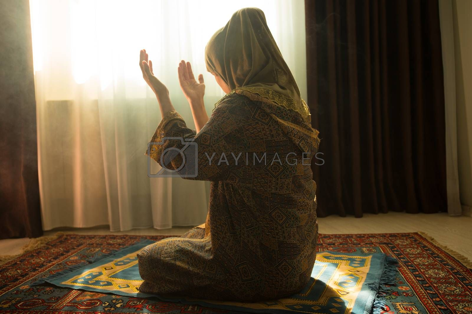 Muslim woman praying for Allah muslim god at room near window. Hands of muslim woman on the carpet praying in traditional wearing clothes, Woman in Hijab, Carpet of Kaaba, Selective focus