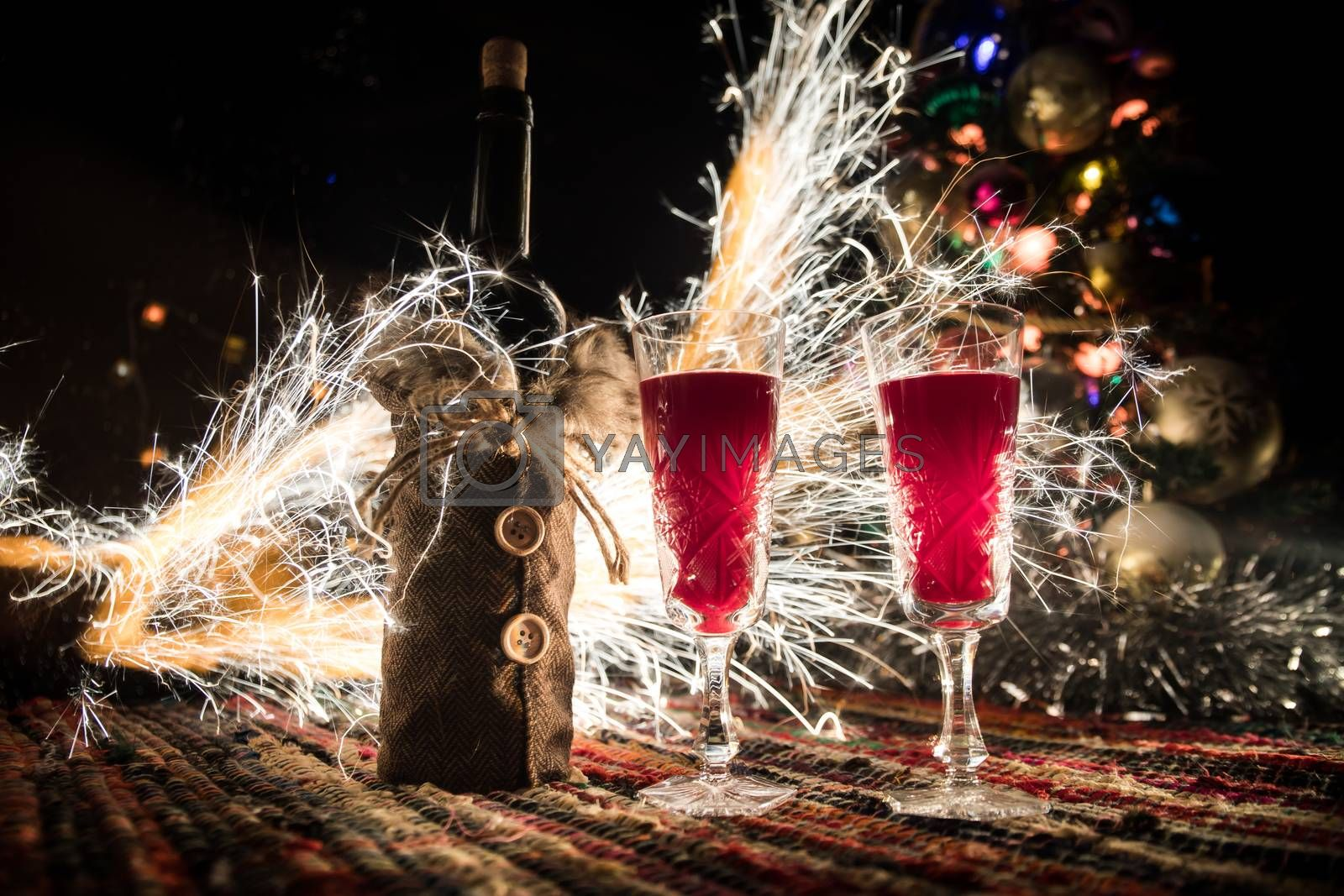 Glass of wine with Christmas decoration. Red wine in crystal glass with bottle on colorful carpet with creative New Year artwork decorations. Copy space