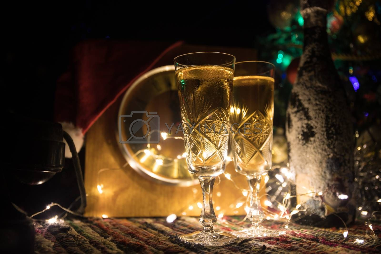 Glass of champagne with Christmas decoration. Traditional winter holiday alcohol drink in snow with creative New Year artwork. Copy space. Selective focus