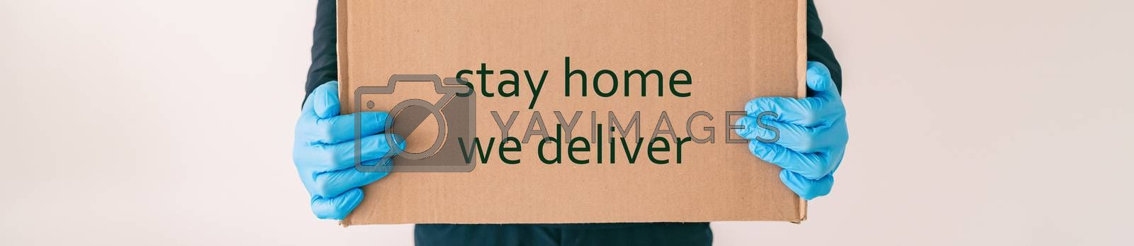 Home delivery with quote STAY HOME WE DELIVER on cardboard box banner. Food grocery delivered with gloves for COVID-19 quarantine from coronavirus social distancing. man giving purchase by Maridav