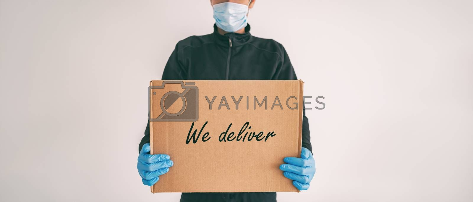 Home delivery WE DELIVER sign on cardboard box banner. Food grocery package online shopping man delivering with gloves and mask for COVID-19 coronavirus social distancing carrying at door by Maridav